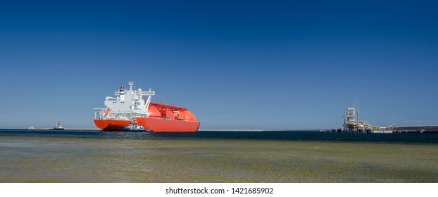 GAS TANKER AND LNG TERMINAL - The big ship maneuvers in the mooring port at the wharf