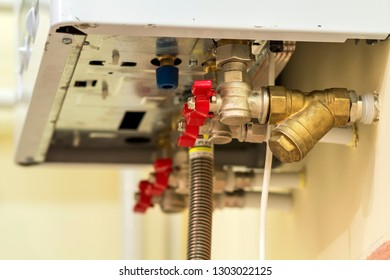 Gas water heater boiler for home heating, bottom view. Installation, connection and maintenance concept.