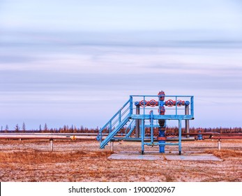 Gas well at sunset. Oil and gas industry. Group bends and fittings, High pressure gas pipe
