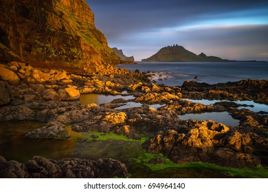 Gasadalur rocky harbour with Tindholmur island in sunset, Faroe Islands