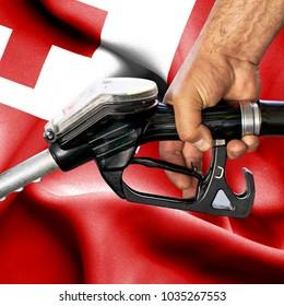 Gasoline consumption concept - Hand holding hose against flag of Tonga