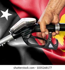 Gasoline consumption concept - Hand holding hose against flag of Papua New Guinea