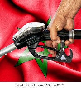 Gasoline consumption concept - Hand holding hose against flag of Morocco