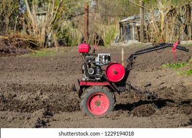 Gasoline cultivator. Motoblock plowing the land with a plow.