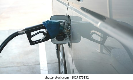 A gasoline dispenser filling to a van in gas station after loan road trip.