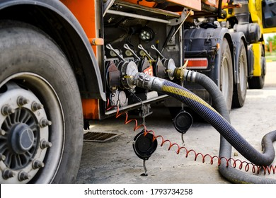 A gasoline tanker pours gasoline into an underground tank.