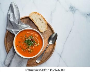Gaspacho-Suppe auf einem runden Holzfach auf weißem Marmortisch. Schüssel mit traditioneller spanischer kalter Suppe pur Gazpacho auf hellmarmor Hintergrund. Kopiert Platz für Text oder Design. Draufsicht oder flache Lage.
