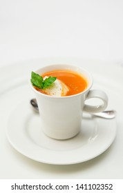 Gaspacho soup served in coffee cup with whipped cream and basil leaf