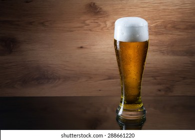 Gass of beer on wooden background with copyspace