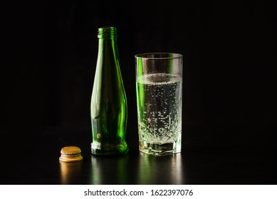 Gassed water in a glass on a black table and black background. Glass of water