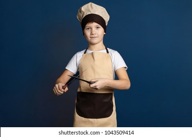 Gastronomy, cooking, catering and food industry concept. Studio shot of handsome cute 10 year old boy dressed in chef uniform sharpening knife with another one. Male child honing kitchen knives