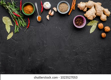 Gastronomy, culinary. Secrets of tasty dishes. Seasoning and spices. Rosemary, ginger, chili pepper on black background top view copy space