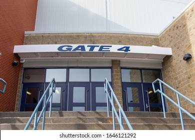 Gate 4 or four entrance to a stadium or concert hall. The walls are brick and orange metal. The sign is white with the words Gate 4 in blue. There are steps up to the multiple glass blue doors.