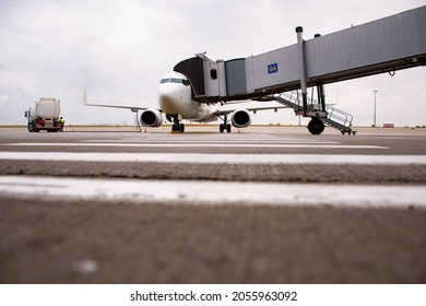 Gate in airport, jet bridge or passenger boarding bridge, with aircraft or plane docked and being refueled; blurred foreground