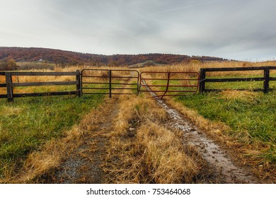 A gate blocks entry to a muddy, primitive country dirt road that appears less traveled.