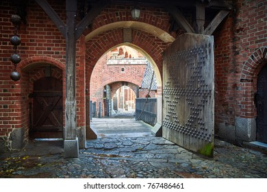 Gate in Castle of the Teutonic Order in Malbork, Poland. Red brick wall and cobblestone
