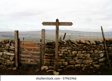 Gate in a drystone wall on Pen-y-ghent in the Yorkshire Dales. Signpost points the way.