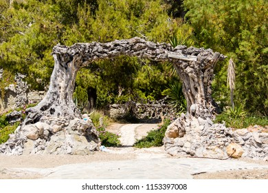 A gate formed by two trunks of tree in a very bizzare way at salamina island, Greece