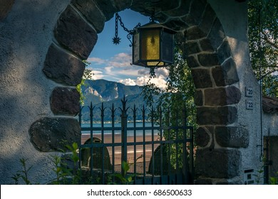 Gate of a house with a latern in the arch. Looking through the gate you can see a lake and mutains on a sunny day with blue sky and some clouds.