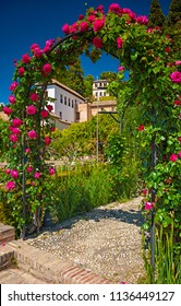 Gate made of red roses in the park of Generalife, Granada, Spain