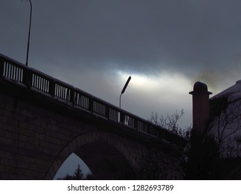 The gate to oblivion concept. Bridge, a street light and the smoke from a house chimney on a overcast winter day
