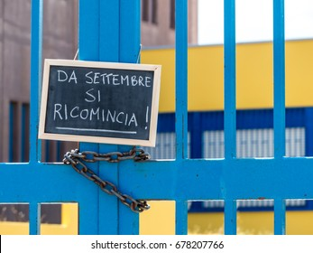 """a gate school closed and a chalkboard hanged  on it. the gate is closed by a chain and on the chalkboard is written, in italian words, """"It starts again in September"""""""