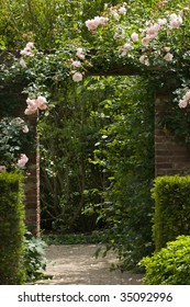Gate in stone wall in the garden with pink climbing rose New Dawn
