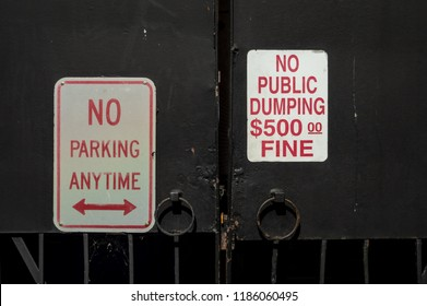 A gate with two signs. One sign says no public dumping and no parking anytime.