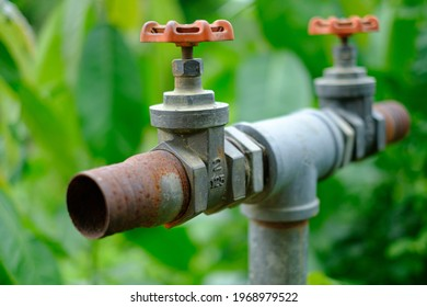 Gate valve on the pipeline in irrigation systems control the water to close the old place at blur background
