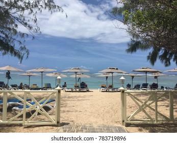 Gate to the white sand beach of Saint Gilles Les Baines in La Réunion Island wir beach chairs and beach umbrellas