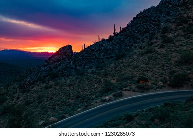 Gates Pass road with a beautifully colored desert sunset sky, pinks, purples. Saguaro cactus, cholla cacti and ocotillo. Silhouettes on ridge top  Trail leads up to rocky overlook. Tucson, Arizona.