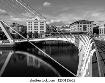 Gateshead, England. UK. October 18, 2018. People walking over Gateshead millennium bridge on the quayside with bridge reflection in the river tyne. The bridge connects Gateshead with Newcastle.
