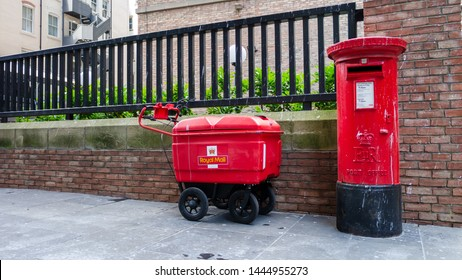 Gateshead, United Kingdom - July 8th 2019: Royal Mail/Post Office Red Pillar Post Box with Royal Mail package carrier or cart.