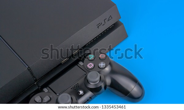 Gateshead, United Kingdom - March 11th 2019: Sony Playstation PS4 console including official Sony Dual Shock controller.  Studio shot and featured on a vibrant blue background.