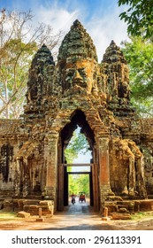 Gateway to ancient Angkor Thom in Siem Reap, Cambodia. Gopura with stone face on woods background. Enigmatic Angkor Thom is a popular tourist attraction.