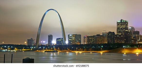 The Gateway Arch and skyline of St Louis overlooking the Mississippi River illuminated at night