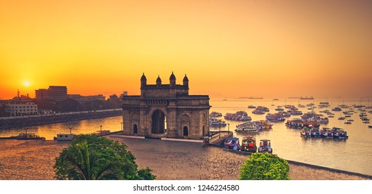 The gateway of India at sunrise with beautiful reflections in the sea. Boats in the water in a hot day.