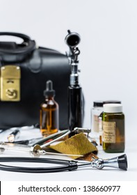A gathering of antique doctors instruments and tools along with a black vintage doctors bag