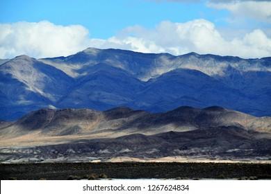 Gathering clouds cast shadows across a mountainous desert expanse.