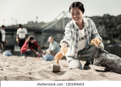 Gathering cups. Smiling socially active woman wearing bright yellow gloves gather empty coffee cups on beach