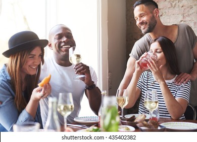 Gathering of four diverse laughing adults enjoying wine and appetizers at lunch with each other at restaurant table beside large bright window