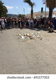 Gathering in homage to victims of Nice terrorist attack on the 14th of July 2016 express disgust by throwing garbage and spitting on the spot where the truck was stopped/Anger over victims in Nice