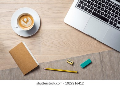 Gathering of office supply such as laptop, notebook, ruler, pencil and rubber with coffee cup lying on office desk as flat lay from bird's eye view