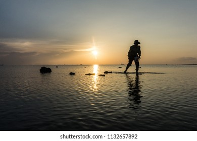 Gathering shells on the shallows in the Gulf of Thailand at sunset. East coast of the island of Phangan, Thailand
