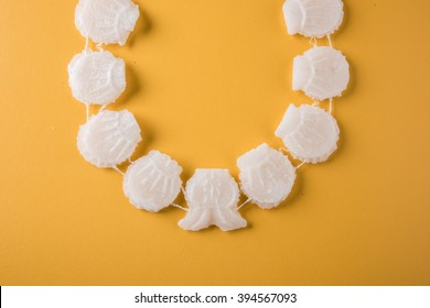 Gathi is a necklace or a strand made up of sugar crystals. It's a tradition in holi and gudi padwa festival to wear this Mala. This also protects from sun stroke. over colourful or wooden background.