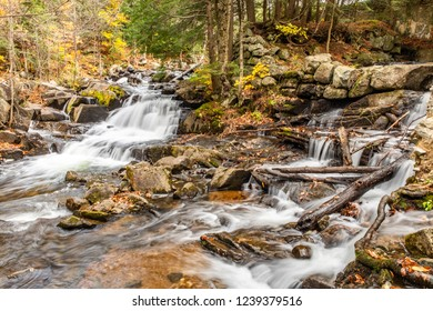 In Gatineau Park Quebec, two waterfalls, side by side, run down the rocks and over the autumn leaves near the Carbide Willson ruins.
