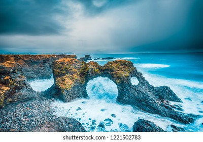 Gatklettur Arch rock, Snæfellsnes Peninsula. Dramatic mossy cliffs in front of blue ocean in Arnarstapi, Iceland