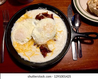 Gatlinburg, Tennessee, USA - January 1, 2019: A hot skillet breakfast of eggs, bacon, cheese, and grits is served to a customer at a Flapjack's Pancake Cabin restaurant in the Great Smokies.