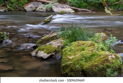 Gatlinburg, Tennessee, USA. Moss covered rocks and boulders obstruct the flowing waters of a rivulet leading into the Nantahla river in summer near Gatlinburg, Tennessee, USA.