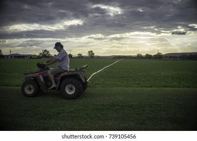 Gatton, Australia, April 2017, a farmer on his evening check of the fields driving his mini tractor